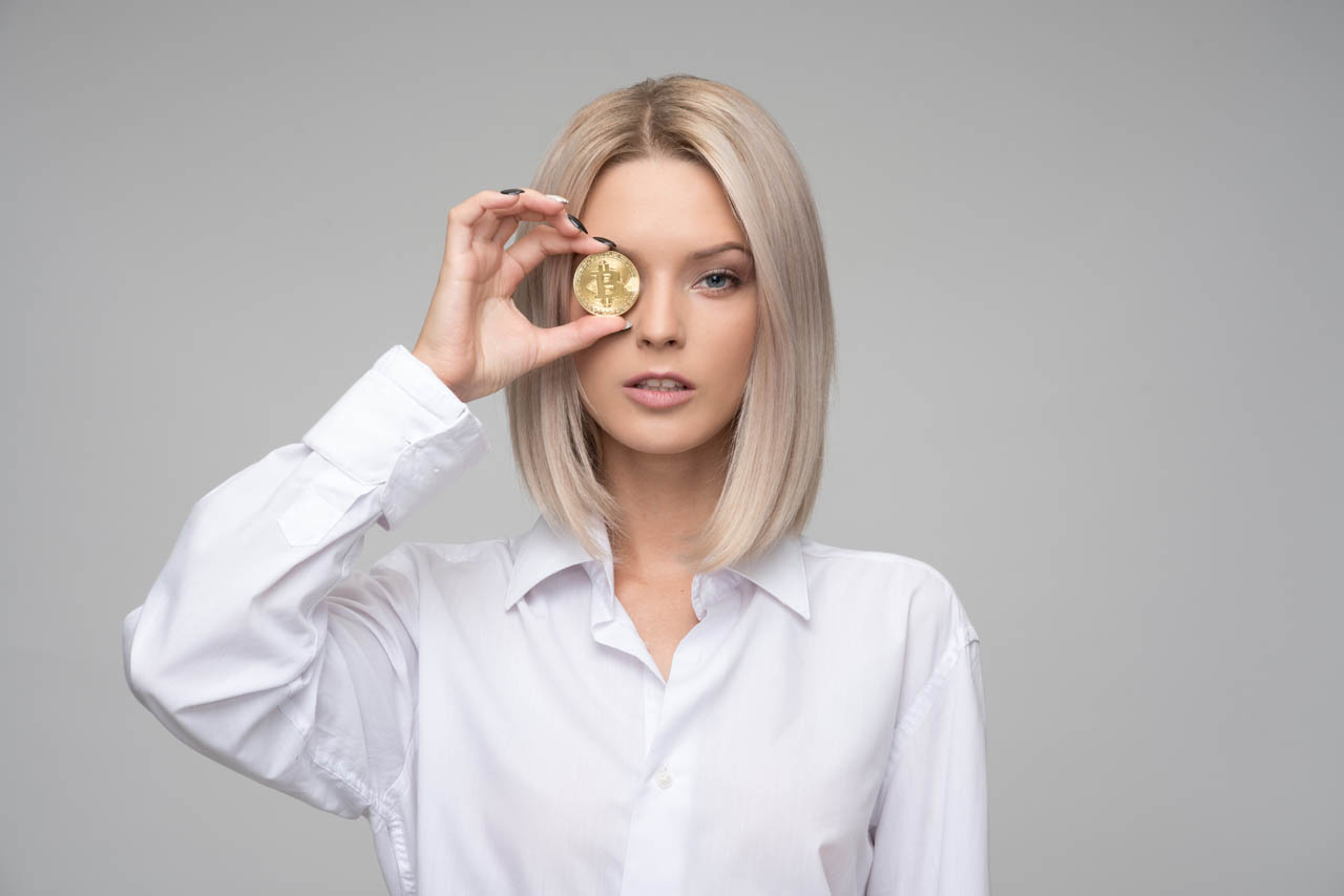"""Blonde girl wearing a white shirt holding a bitcoin"""
