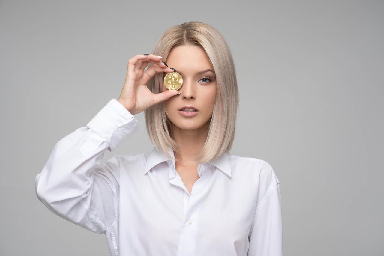 """Blonde girl wearing a white shirt holding a bitcoin"""